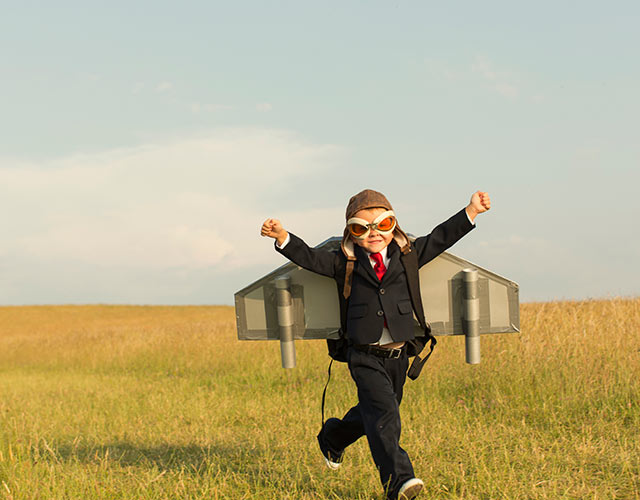 Little boy running through field wearing air plane wings and goggles