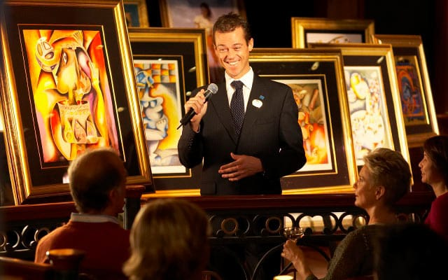 Art Gallery host speaking to crowd with fine art behind him