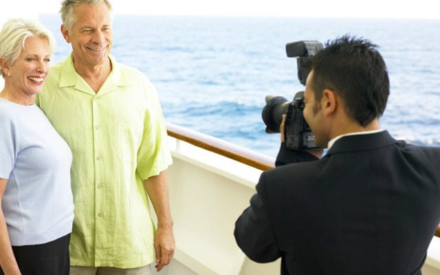 Photographer Taking A Picture Of Couple On Deck