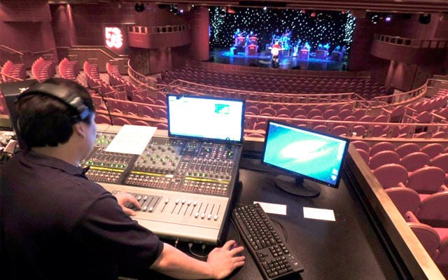 A Production Technician sitting behind the console in the theater