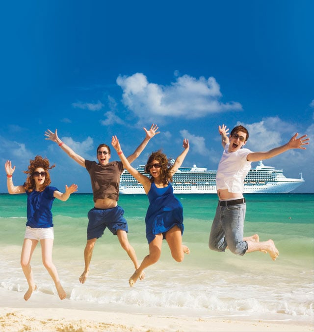 Four people on a beach jumping with ship in the background