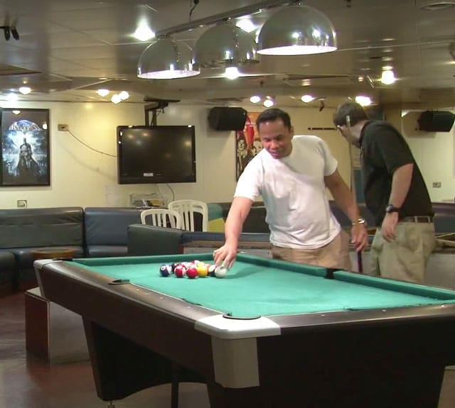 A couple of crew members playing billiards in recreation room