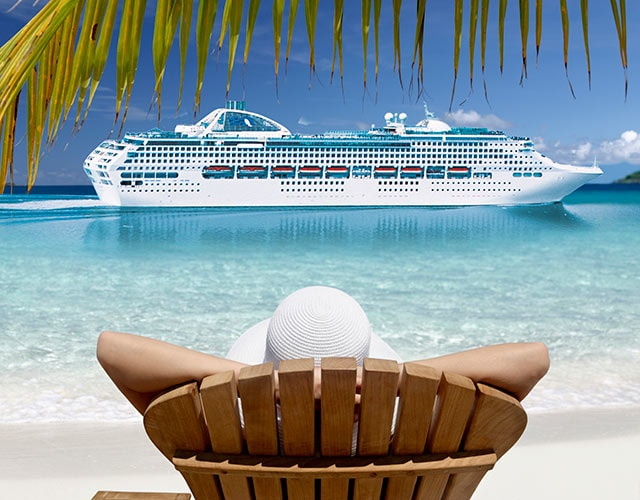 Guest relaxing in a beach chair on the beach overlooking clear blue water with a Princess ship