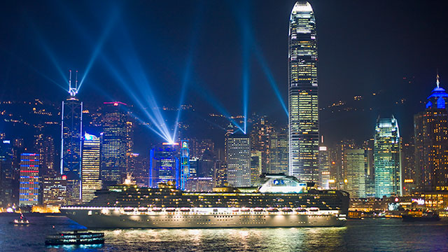 Ship in from of Hong Kong skyscrapers at night