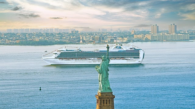 ship sailing by New York City and Statue of Liberty