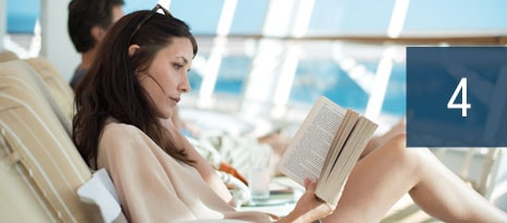 4 - woman reading a book while relaxing in a lounge chair on deck