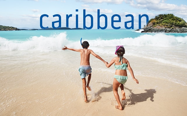 caribbean. Children in swim gear running towards the ocean.