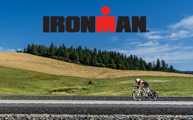 a bicyclist riding on the road with hills and trees in the background. IRONMAN logo on top.