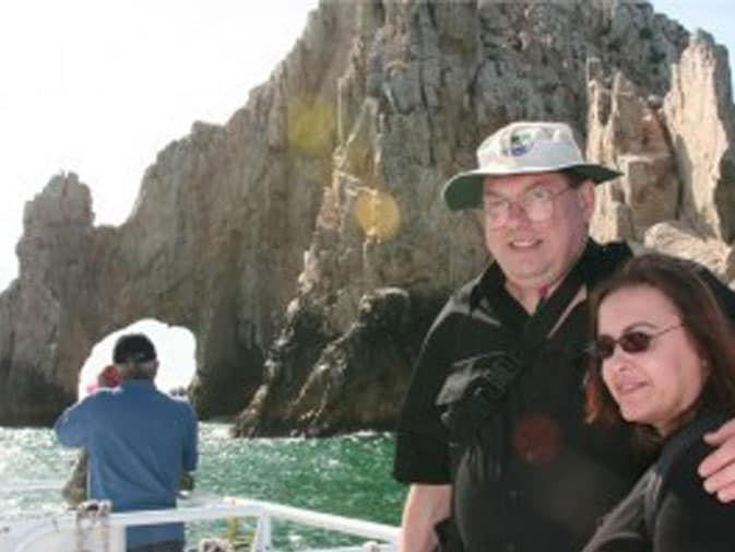 Ashley and her husband pose in front of the Arch in Cabo San Lucas