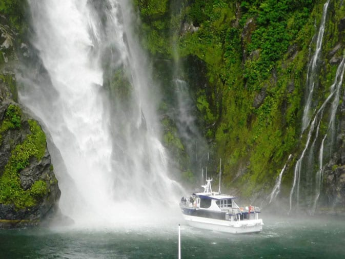 A tour boat ventures towards the waterfalls in Milford Sound