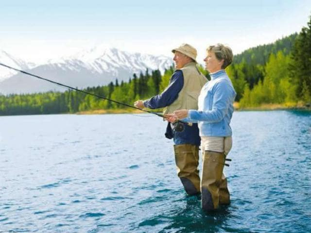 A couple enjoys fly fishing during their Alaskan vacation.