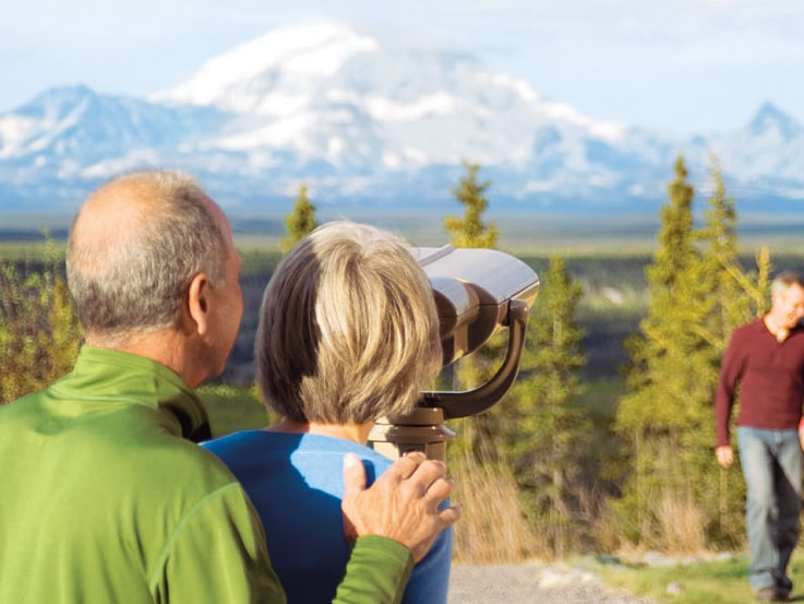 A couple enjoys the vista of the Wrangell Mountains while on a cruise to Alaska.