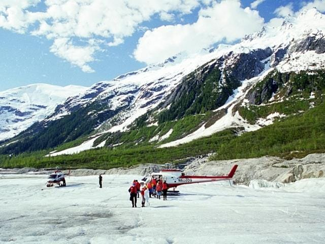 Cruise passengers walking on a glacier in Alaska on a helicopter tour.