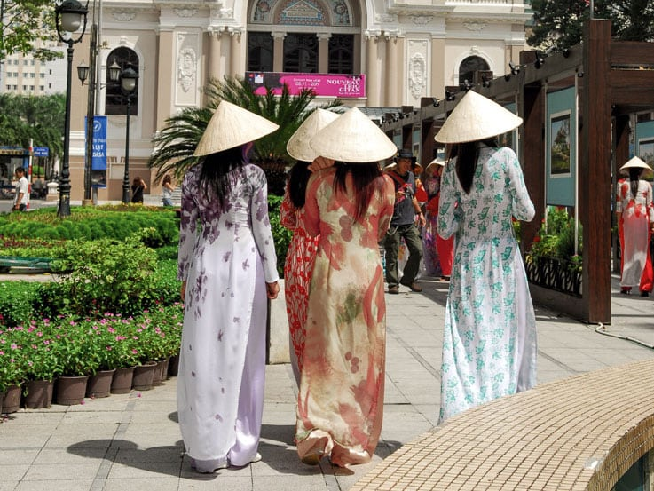 Women dressed in traditional Vietnamese attire while walking in Ho Chi Minh City, Vietnam
