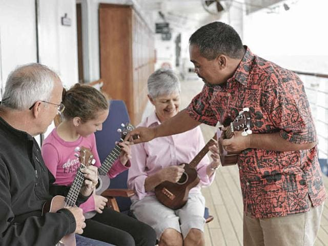 A family takes a ukulele lesson together on board their Hawaiian cruise ship.