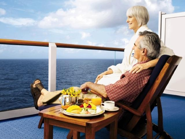 A couple enjoys view from their cruise ship cabin balcony.