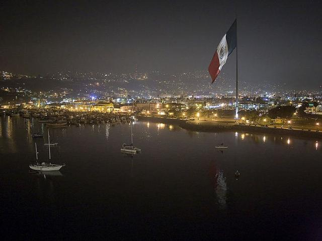 The biggest Mexican flag in the country flies over Ensenada at night.