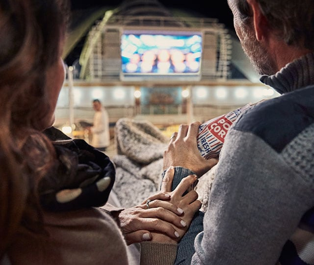 couple watching movie under the stars while sharing popcorn