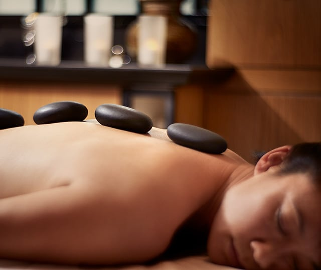 woman laying on massage table in spa relaxing while receiving hot stone massage