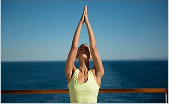 a women doing yoga on the top deck of a ship with the ocean in the background