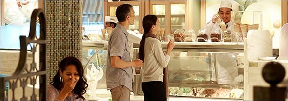 A couple ordering ice-cream onboard while another woman in the foreground is enjoying a treat