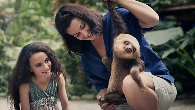 Woman holding a sloth in Costa Rica while a child watches.
