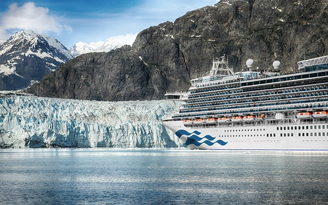 Cruise ship at sea with large glacier and mountains.