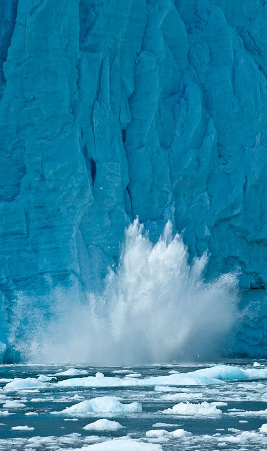 A falling piece of glacier splashes in the waters of Glacier Bay