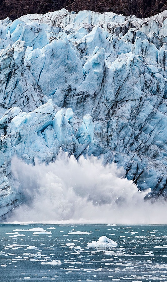 A falling piece of glacier splashes in the water
