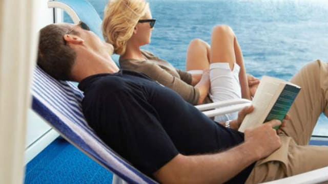 a man and woman sitting in lounge chairs onboard a cruise ship