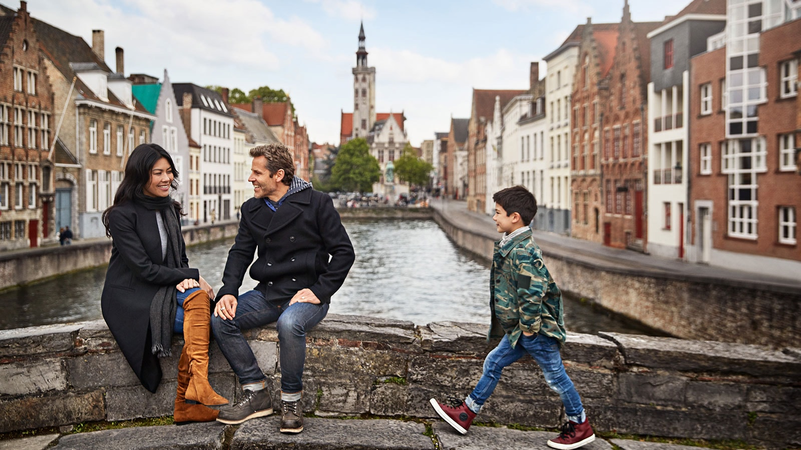 A couple smiling and sitting on the bridge with their son walking to them