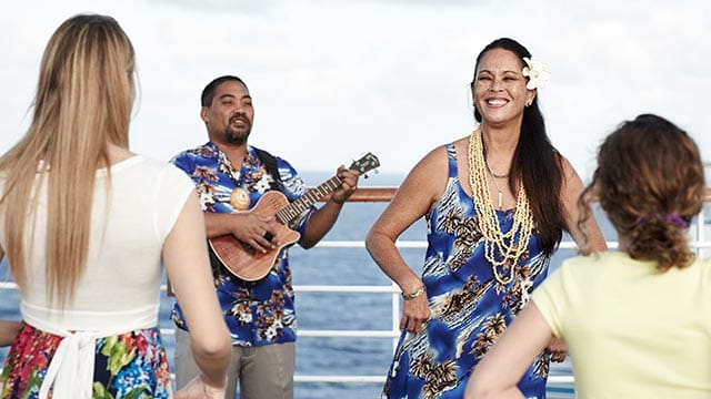 Duo of man playing ukelele and woman performing traditional Hawaiian dance for guests onboard.