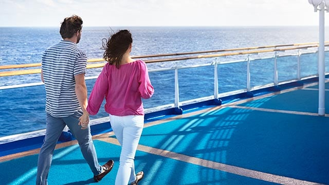 couple holding hands while they walk together on deck.
