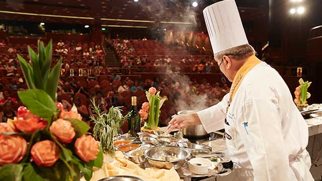 Chef performing cooking demonstration on stage of auditorium