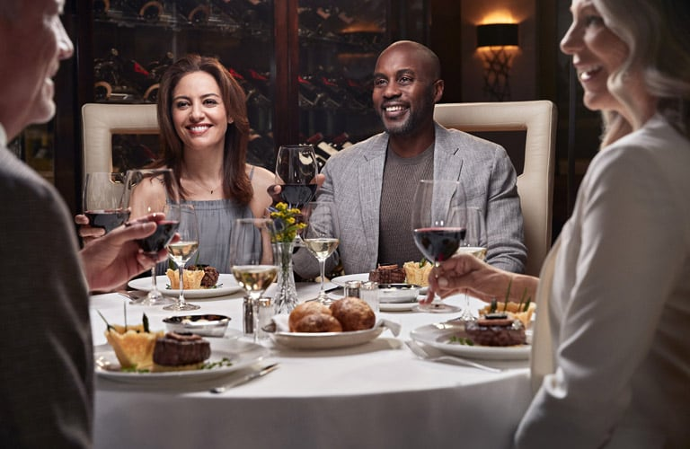 Couples toasting wine at dinner on a Princess cruise.