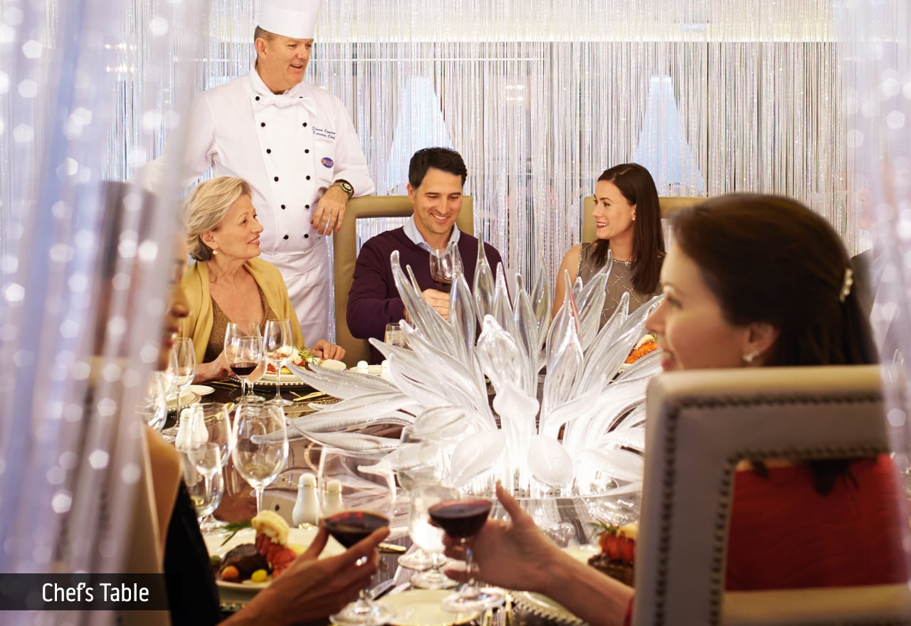 Chef visiting guests at the chef's table onboard a Princess Cruise ship. The table has a glass sculpture in the middle and several people enjoying food and wine.