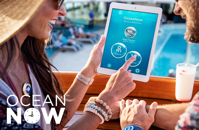 ocean now tm - a couple poolside looking at tablet