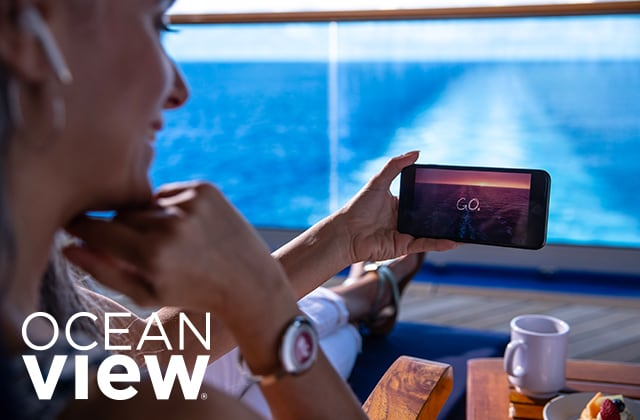 ocean view - woman sitting down wtching a video on her phone with the ocean in the background