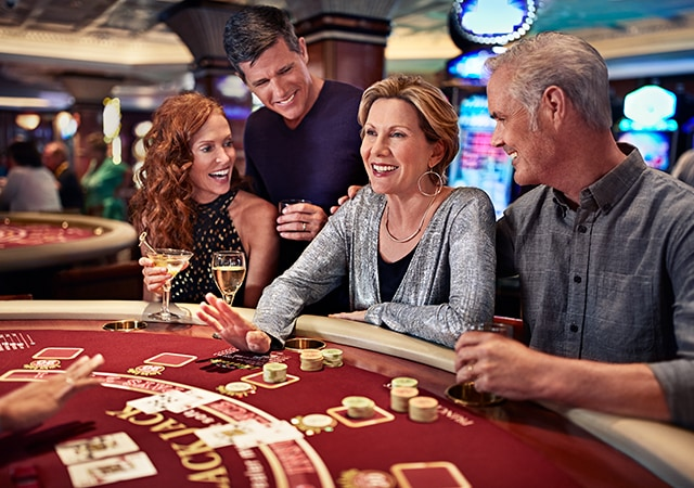 two couples enjoying a game of blackjack with a couple of drinks