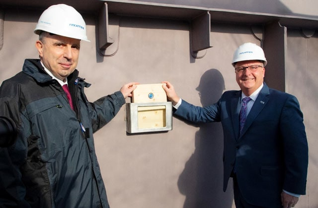 Two men wearing construction hats, posing with a piece of wood holding an Ocean Medallion