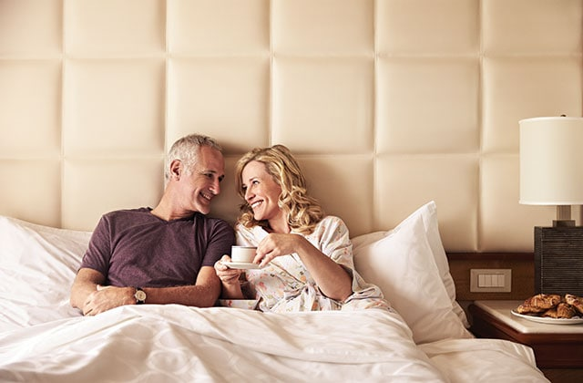 a couple relaxing in bed in a well appointed stateroom onboard a princess cruises ship