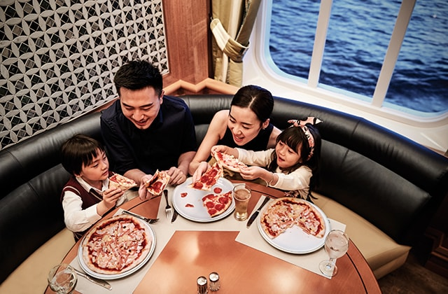 a family sitting around a table indulging the personal pizzas made from the onboard pizzeria