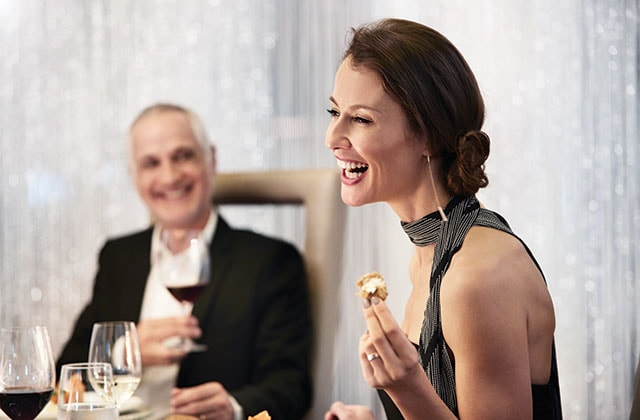 a women holding a delightful bite sitting at the specialty dining chefs table onboard a princess ship