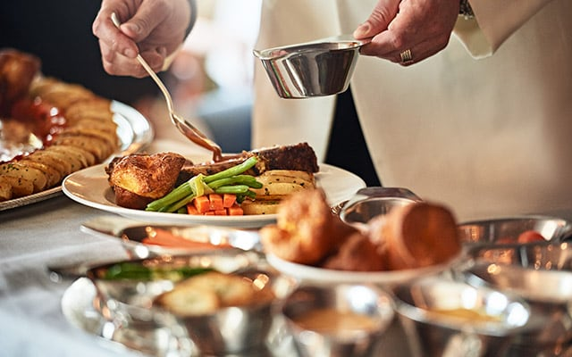 Preparing a dish of roast beef and vegetables tableside
