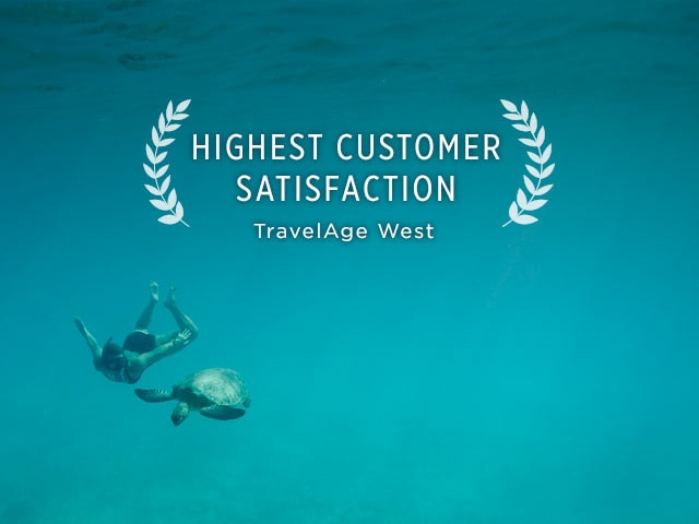 Highest Customer Satisfaction accolade from TravelAge West. Woman snorkeling underwater, swimming alongside sea turtle.