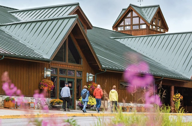 people walking in front of a princess owned Alaska lodge which can be booked with a cruisetour