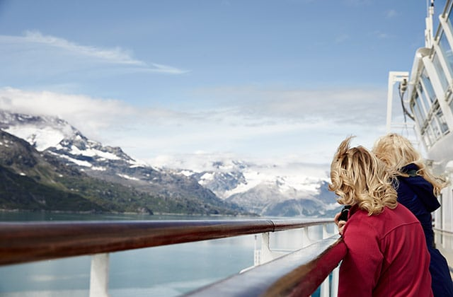 2 ladies looking over a rail on the top deck of a princess ship on a Alaska cruise