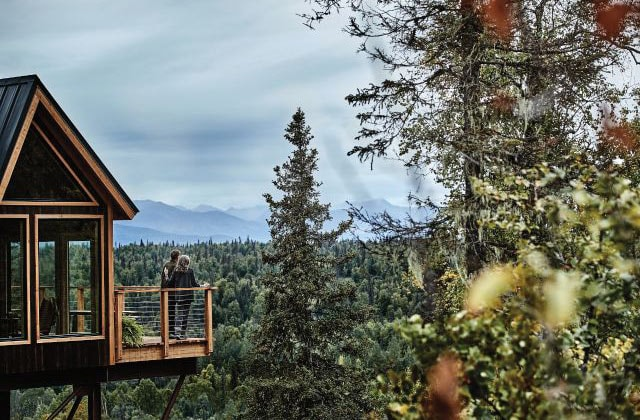 A couple enjoys the view from the deck of a treehouse