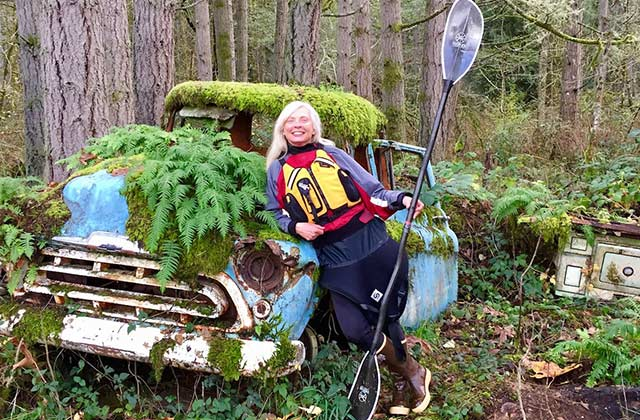 Susan Conrad posing in her kayaking gear, leaning agains an old pickup truck being swallowed by the forest.