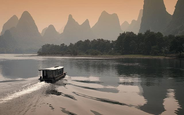 small boat on a lake with surrounding mountains in Asia
